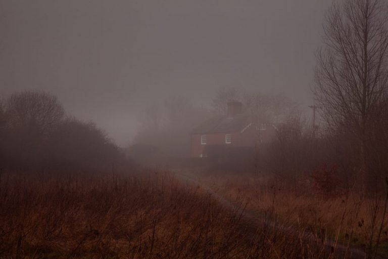 huanted creepy csary house in the fog mist