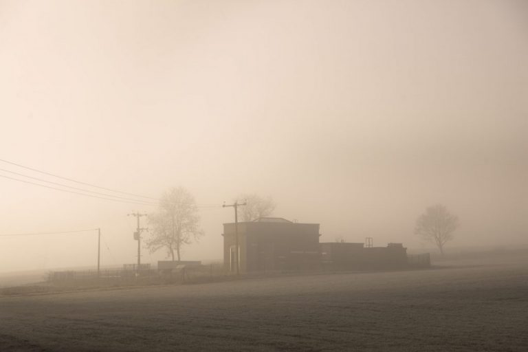 foggy field with building